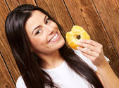 Portrait of young woman eating a donut against a wooden wall — Stock Photo