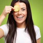 Portrait of young woman holding a potato chip in front of her ey — Stock Photo