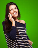 Young woman talking on mobile over green background — Stock Photo