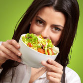 Portrait of young woman holding a fresh salad over green — Stock Photo