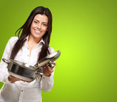 Portrait of young girl opening sauce pan over green background — Stock Photo