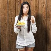 молодая женщина, едят картофельные чипсы на деревянных фоне — Стоковое фото