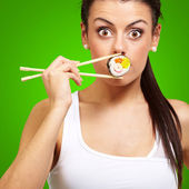 Young woman covering her mouth with a sushi piece against a gree — Stock Photo