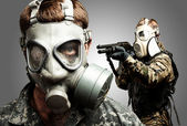 Young soldiers wearing gas mask over grey background — Stock Photo