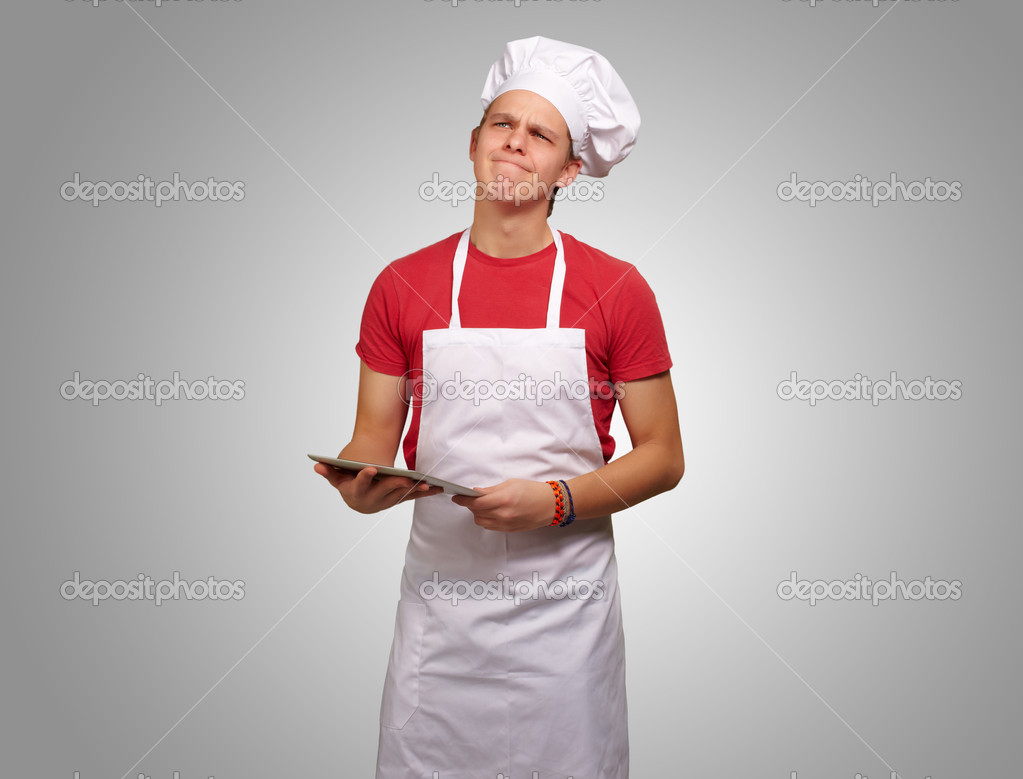 Portrait of young cook man holding a digital tablet and thinking over grey background  Stock Photo #10180636