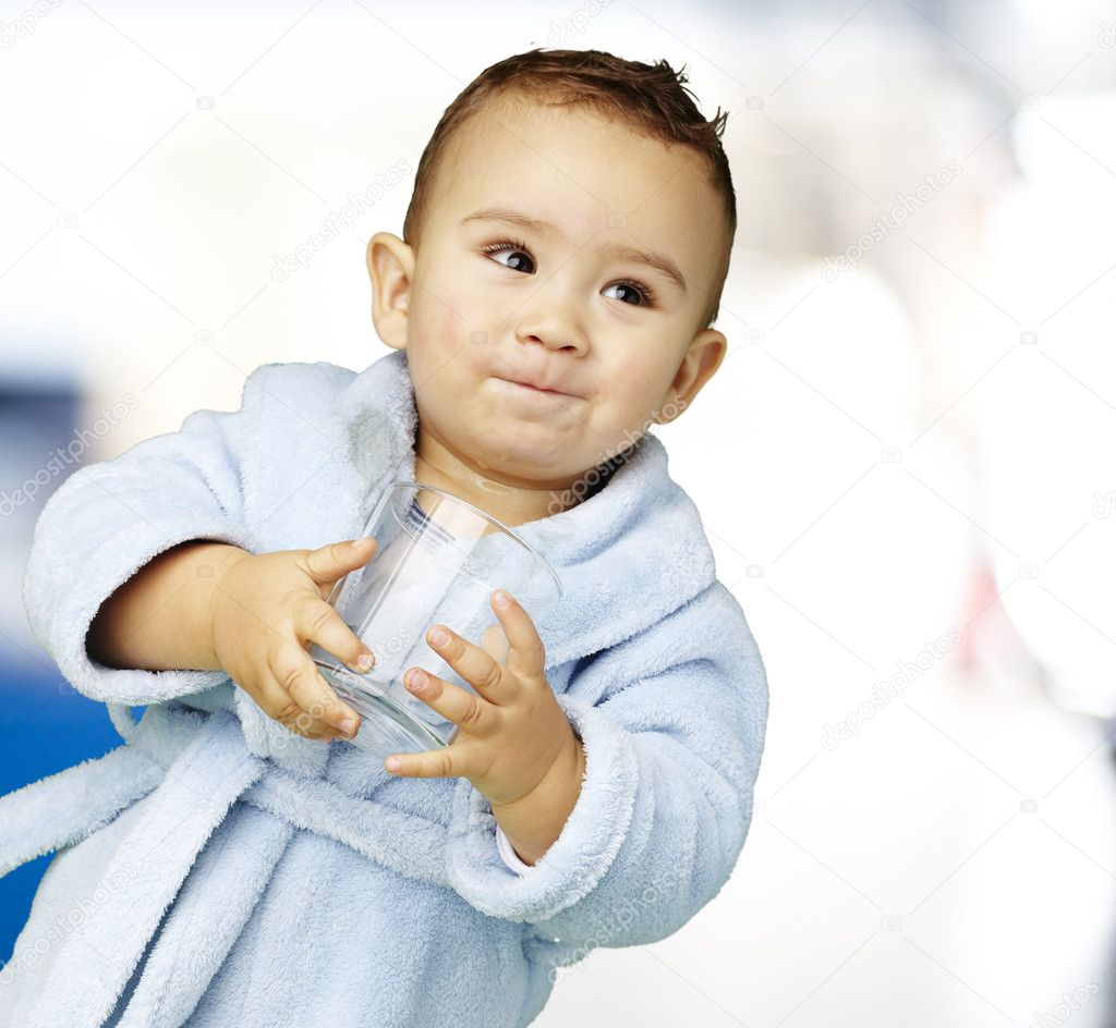 Portrait of an adorable infant with a blue bathrobe holding a glass — Stock Photo #10181122