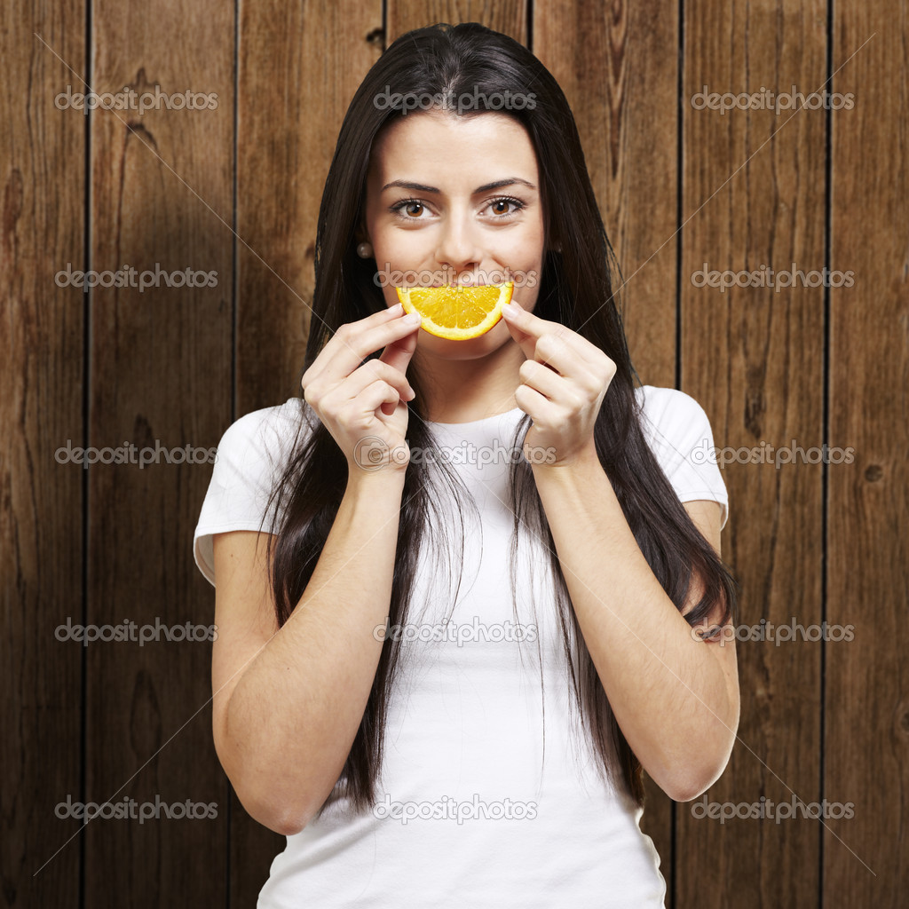 Woman with an orange slice as a smile against a wooden background  Stock Photo #10181632