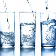 Pouring water in a glass collection isolated — Stock Photo