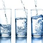 gießen Wasser in eine Glas-Sammlung isoliert — Stockfoto