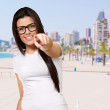 Portrait of young woman pointing with finger against a beach — Stock Photo #10359394