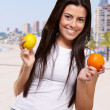 Young pretty girl holding orange and lemon at beach — Stock Photo #10359423