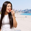 Portrait of young woman eating strawberry against a beach — Stock Photo