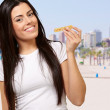 Portrait of young woman eating cereal bar against a beach — Stock Photo