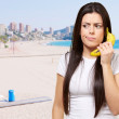 Portrait of young woman calling using banana against a beach — Stock Photo #10359476