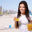 Portrait of young girl drinking orange juice against a beach — Stock Photo