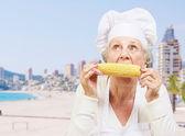 Portrait of senior cook woman eating corn cob against a beach — Stock Photo