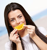 Portrait of young woman holding orange slice against a beach — Stock Photo