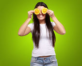 Portrait of young woman holding orange slices in front of her ey — Stock Photo