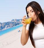 Retrato de jovem contra uma praia a beber sumo de laranja — Fotografia Stock