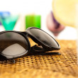 Sunglasses on wicker — Stock Photo