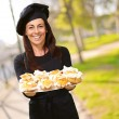 Portrait of middle aged woman holding a delicious muffins at par — Foto Stock