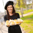 Portrait of middle aged woman holding a delicious muffins at par — Stockfoto