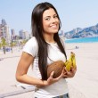 Portrait of young woman holding tropical fruit near the beach — Stock Photo