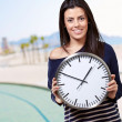 Portrait of young woman holding clock against the beach — Foto de Stock