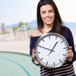 Portrait of young woman holding clock against the beach — ストック写真
