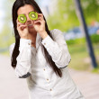 Portrait of pretty woman holding kiwi slices in front of her eye — Stock Photo #10404391