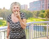 Portret van senior vrouw een granen bar eten tegen een park — Stockfoto