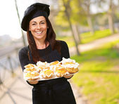 Portrait of middle aged woman holding a delicious muffins at par — Stock Photo
