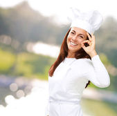 Portrait of middle aged cook woman doing good symbol at park — Stock Photo