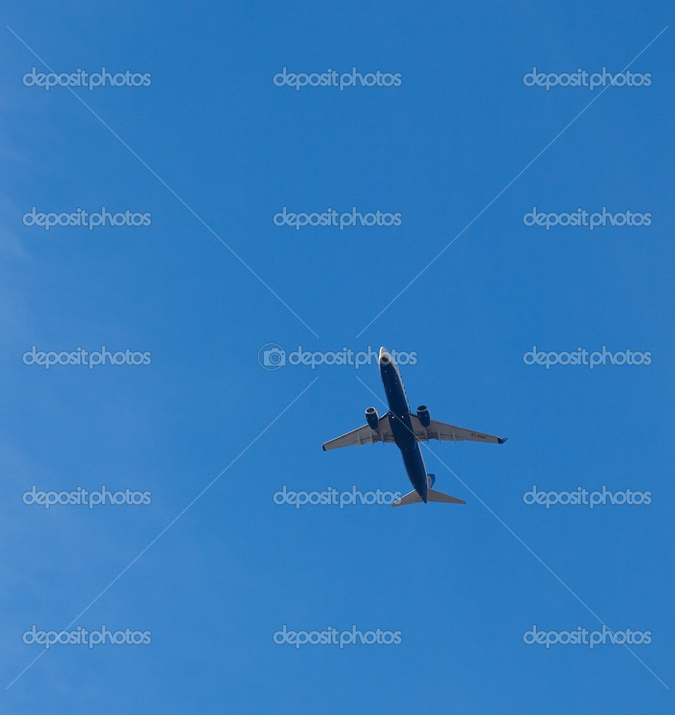 Airplane flying under a blue sky, closeup — Stock Photo #10561122