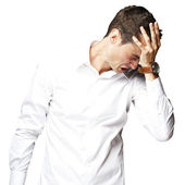 Angry young man doing frustration gesture over white background — Stock Photo