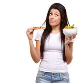 Portrait of young woman choosing pizza or salad against a white — Stock Photo