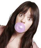 Young girl with a pink bubble of chewing gum against a white bac — Stock Photo