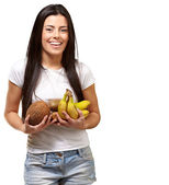 Portrait of young woman holding tropical fruits against a white — Stock Photo