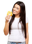 Portrait of young woman eating a donut over white — Stock Photo
