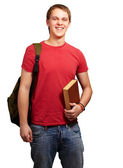 Portrait of young student holding book and carrying backpack ove — Stock fotografie