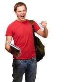 Jonge boos student man afbramen van een blad op witte achtergrond — Stockfoto
