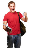 Young angry student man roughing a sheet over white background — Stock Photo