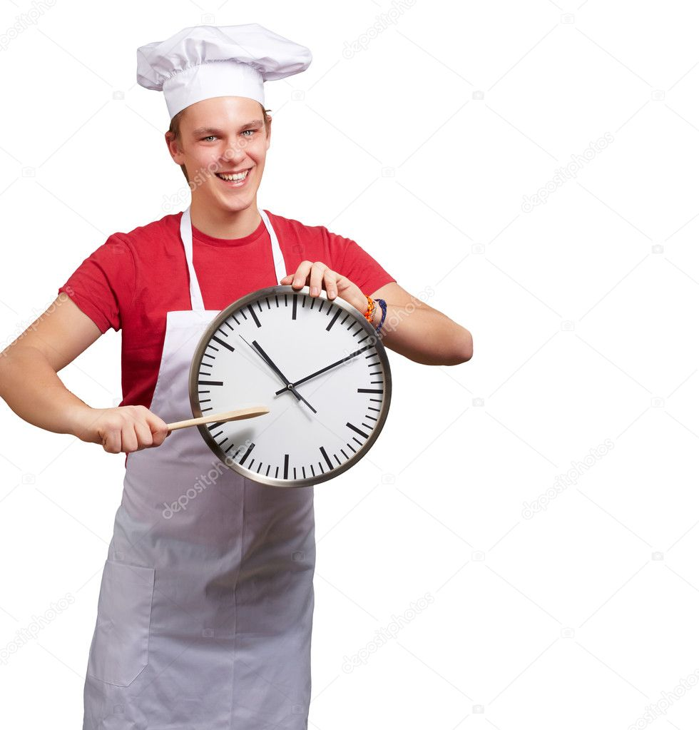 Portrait of young cook man pointing a clock over white background  Stock Photo #10582862