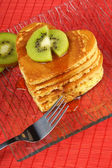Stack of heart-shaped pancakes with syrup and kiwi fruit — Stock Photo