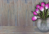 Purple tulips in a wase wooden texture background — Stock Photo