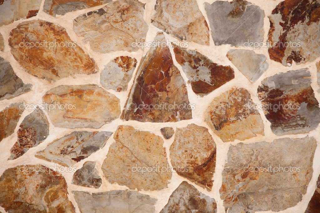 Close up of stone wall with brown and grey irregular shaped blocks cemented together  Stock Photo #9790895