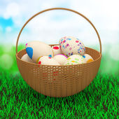Painted Easter Eggs in a basket on a beautiful green grass — Stock Photo