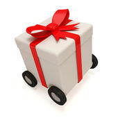Gift Box with Red Ribbon on wheels isolated on white background — Stock Photo