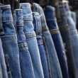 Row of hanged blue jeans — Stock Photo