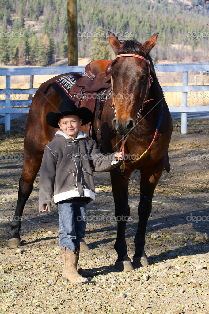 Young boy wearing a cowboy hat with his horse — Stock Photo #8378407